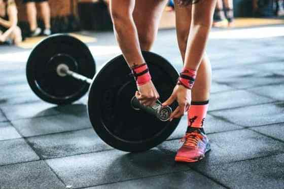 Photo of woman getting ready to deadlift during her fitness routine