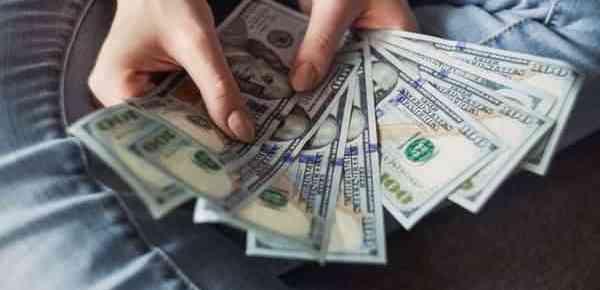Hands holding several dollar financials.