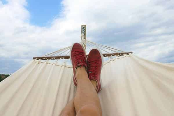 Person relaxing in hammock thinking about dollar financials