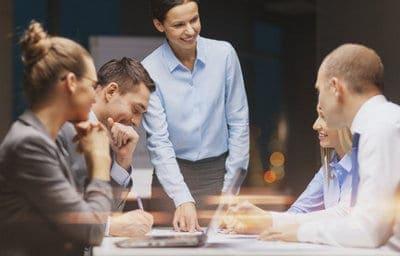 pięciu ludzi przy stole w strojach biznesowych