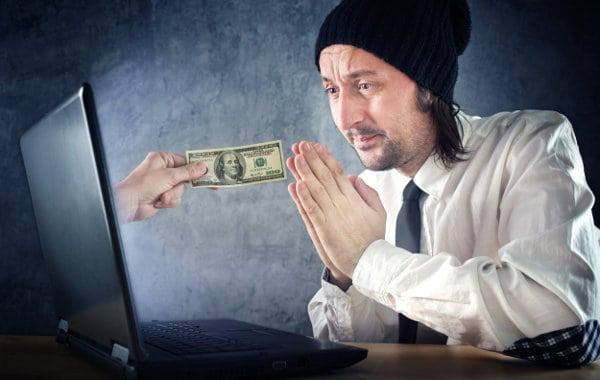 człowiek przed laptopem modli się o pieniądze