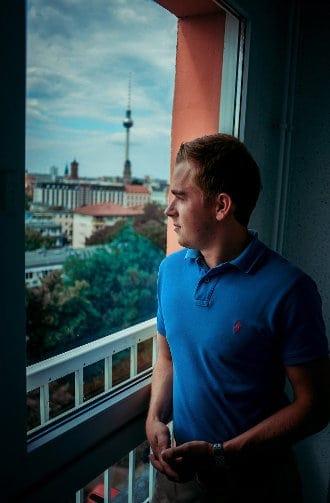 Mężczyzna stoi przed oknem w mieszkaniu i przez nie patrzy
