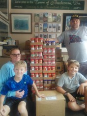 Gavin Price collected nearly 1,400 jars of peanut butter with a bit of help from his family. Gavin, left, his brother, Keegan, and parents, Bill and Cindy Price, stand around jars of the food staple. [SUBMITTED PHOTOS]