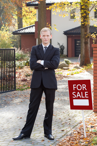 Young attractive real estate broker selling the house