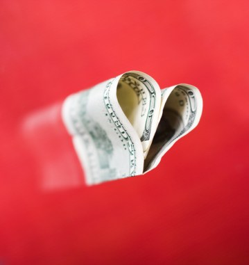Shape of heart from hundred dollars at red background