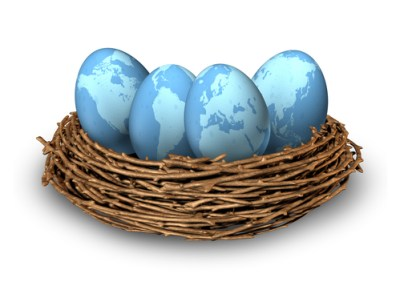 Global investments and international finance business symbol with four blue eggs with the maps of the world in a nest as a concept of savings and money management in many regions as Asia North America Europe and Latin America.