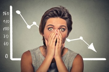 Shocked scared woman with financial market chart graphic going down on grey office wall background. Poor economy concept. Face expression, emotion, reaction