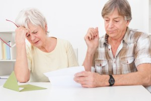 Senior Couple Were Disappointed While Reading Letter On Table