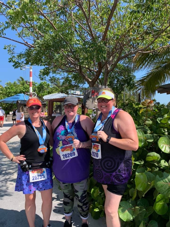 three women with Disney castaway cay 5k finisher medals and race bibs.