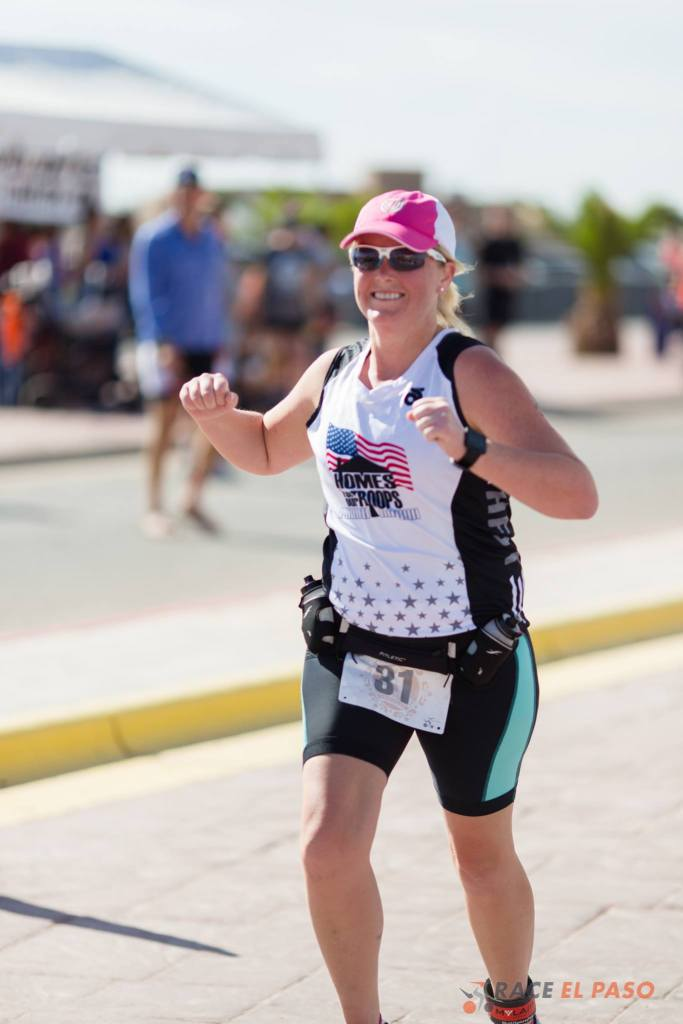 Crossing the finish line at a race in one-piece tri kit with a shirt over it