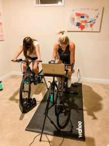 Blonde mother teachers her daughter the value of being consistent as they ride bikes indoors in a basement