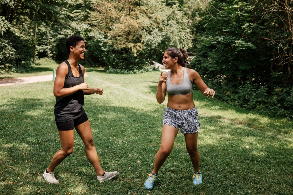 Two women in a sport fitness community exercise in a park