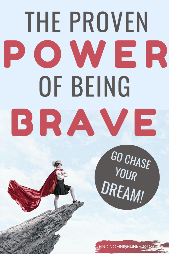A girl in a superhero cape standing on a rock understands the power of being brave.