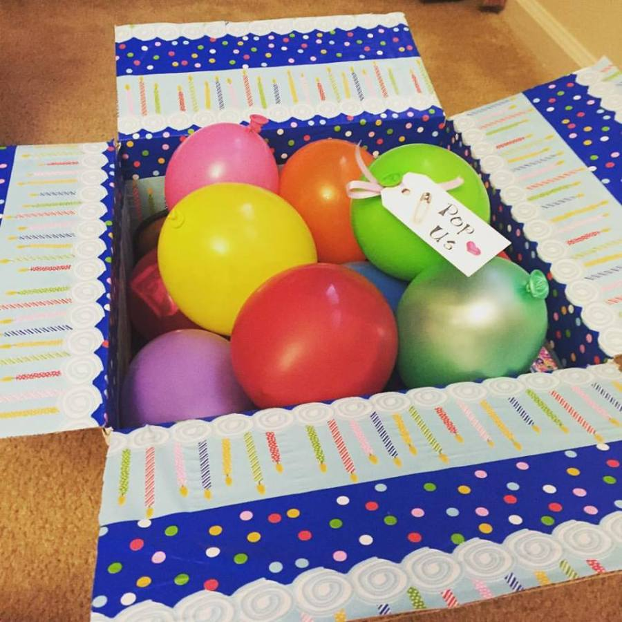 birthday care package with ballons, safety pin, and tag that says Pop Us!