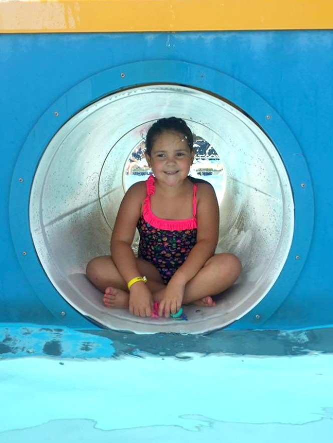 where to swim near Fort Bragg: kid playing on the water playground at Chalmer's Pool in Fayetteville, NC