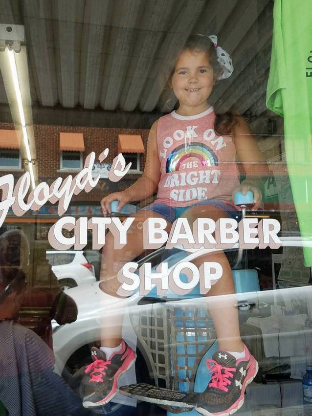 Girls sitting in window at Floyd's Barber Shop