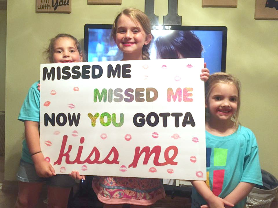 girls making a deployment homecoming sign