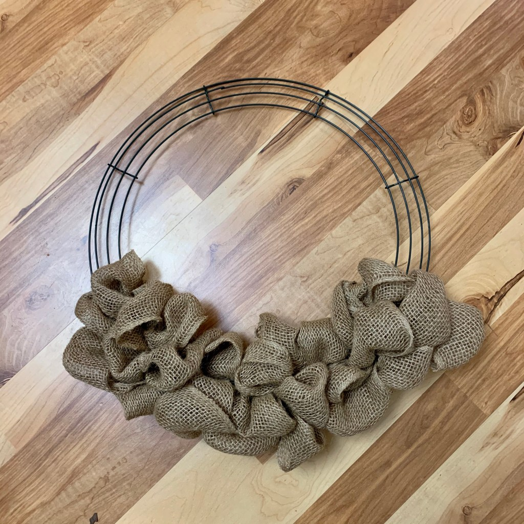 Step 2 of making a Christmas wreath is to add brown burlap to the wreath form.