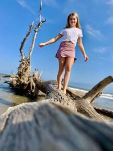 Girl walking on fallen tree at Driftwood Beach, Jekyll Island, Georgia.