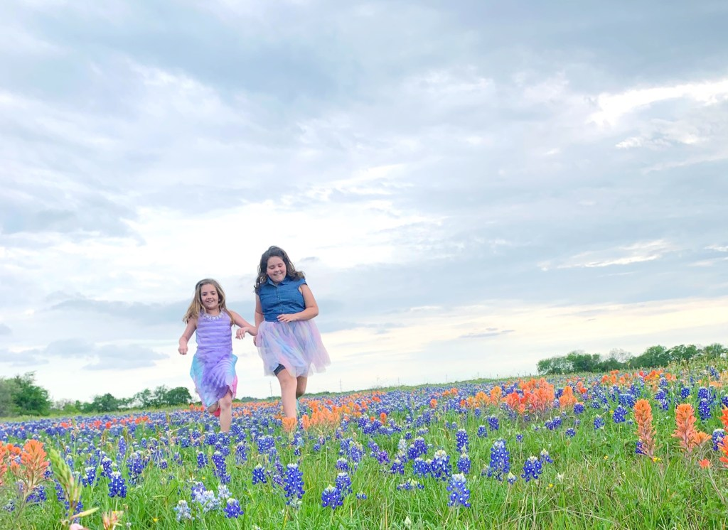 Sisters playing in the bluebonnets