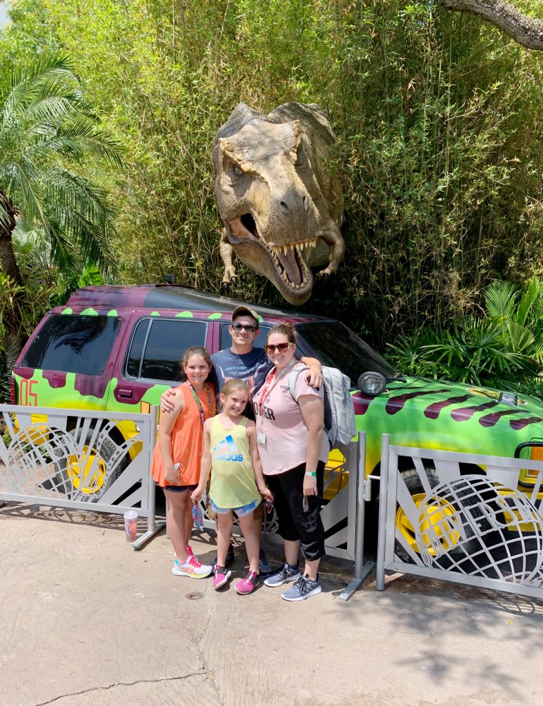 A family photo with a t-rex at Jurassic Park in Islands of Adventure.