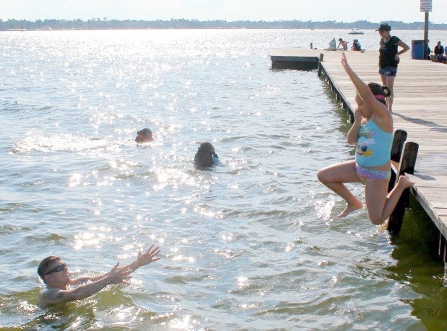 Girl jumping off the dock to her dad at White Lake.