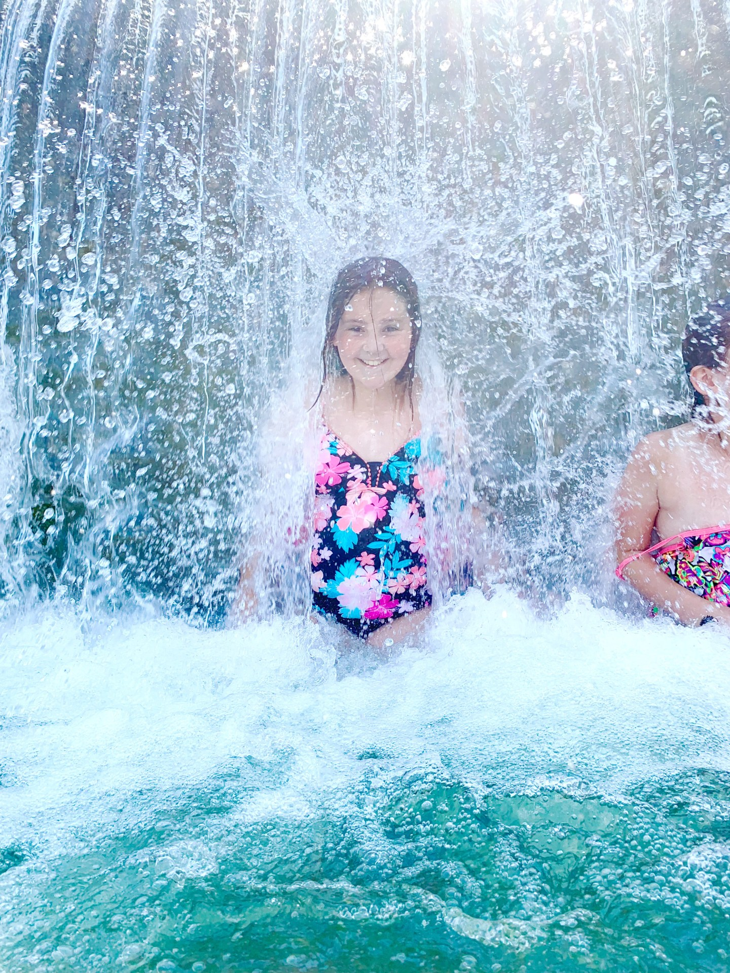 Girl standing under a waterfall at Blue Hole Park.
