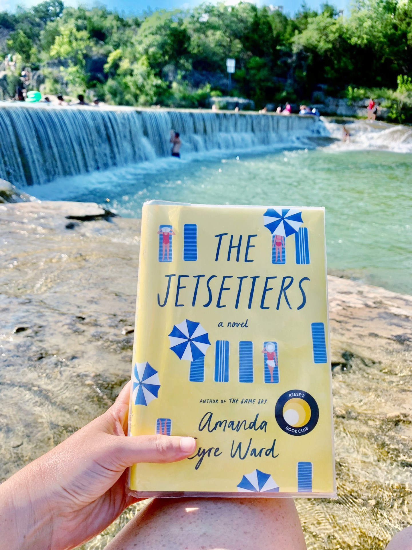Reading the novel 'Jetsetters' while the kids swim in the San Gabriel river.