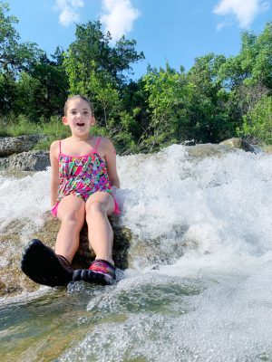 Girl playing in a waterfall in Texas.
