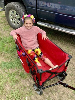 Little girl sitting in wagon at the flea market.