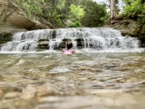 Girl sitting in the water in front of a waterfall near Fort Hood, Texas.