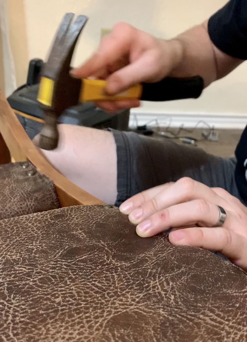Adding upholstery tacks to our refurbished antique rocking chair.