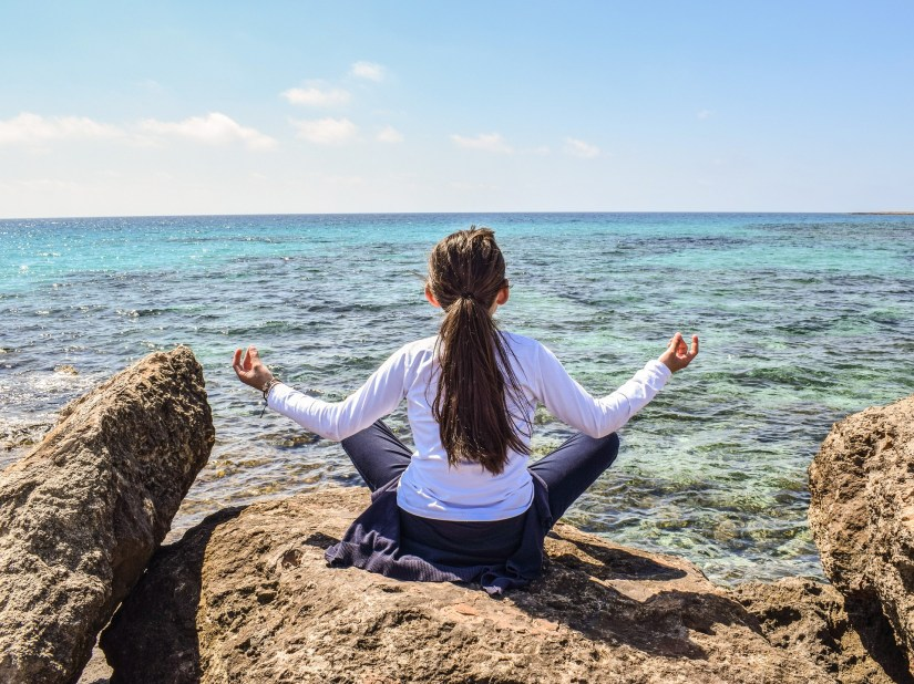 woman long brown hair in a ponytail on rocks at the ocean meditating