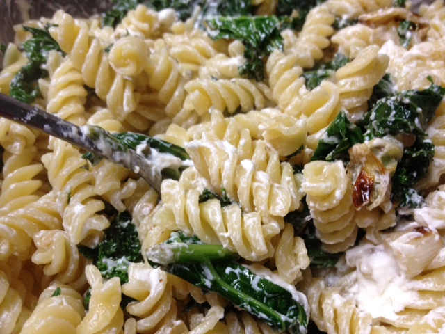 pasta with mixed greens and goat cheese closeup