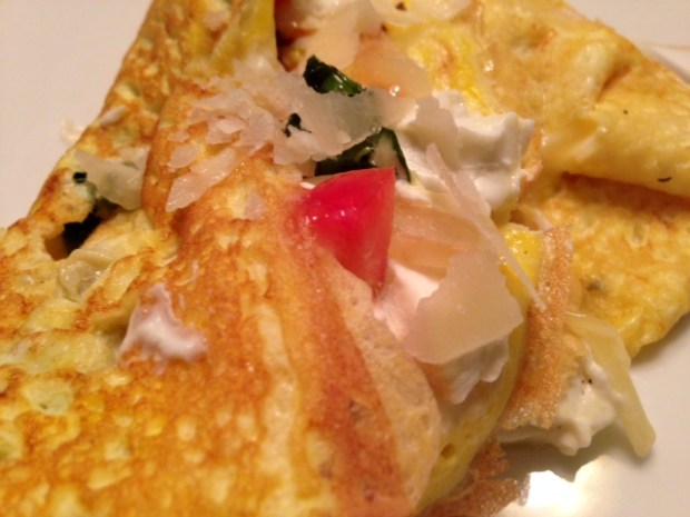 omelette with caramlized onions kale goat cheese closeup