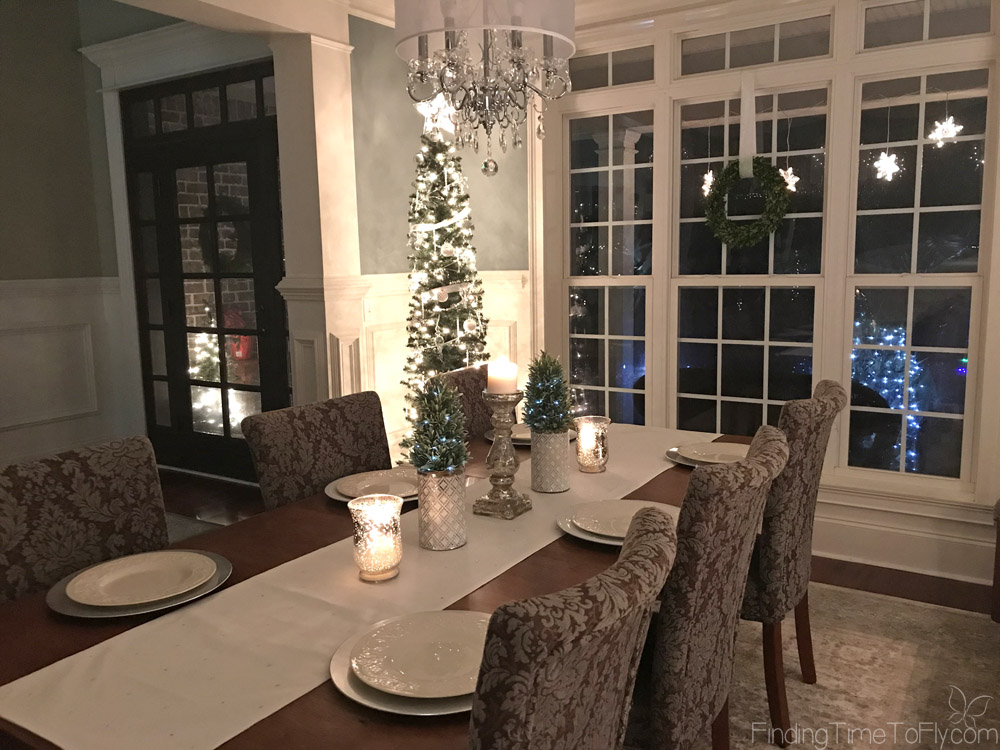 Elegant silver and white Christmas dining room accented with iridescent ribbon, crystals, mercury glass, fairy lights, and a touch of greenery.