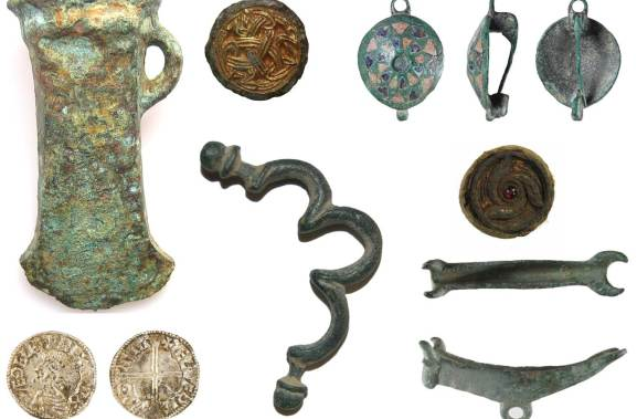 Images of finds found in Cambridgeshire. Top row from left to right: a bronze axehead, a circular gold mount, a circular Roman brooch with red and blue enamel triangles on it. Bottom row from left to right: front and back views of a silver coin, a purse bar, a round lead weight decorated with a garnet stone, a cosmetic mortar with a bull's head.