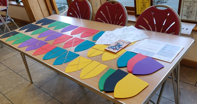 Image showing a table with coloured paper shields for a craft activity.