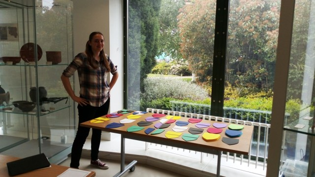Image of a volunteer named Jasmine standing to the left of a long table. A variety of coloured shield shapes are laid out on the table top ready for use in a craft activity.