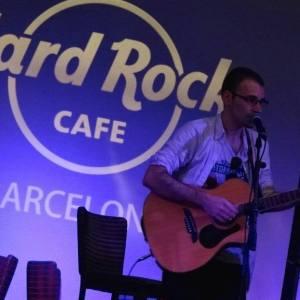 Foto en página oficial de Oscar Martínez frente a un micrófono sujetando su guitarra