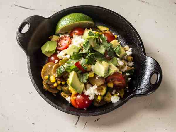 A cast-iron dish of succotash with homemade taco seasoning topped with avocado and cilantro.