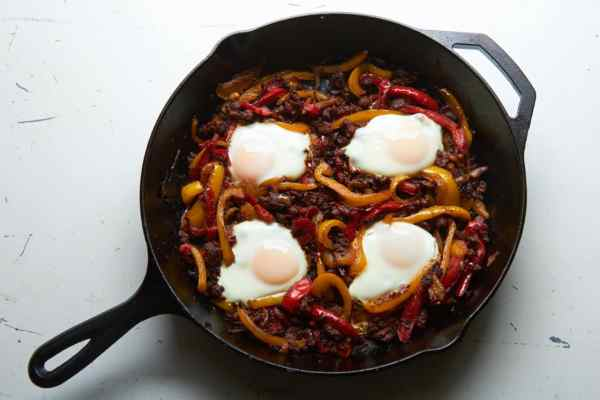 Cast iron skillet filled with piperade - peppers, onions, chorizo and eggs.