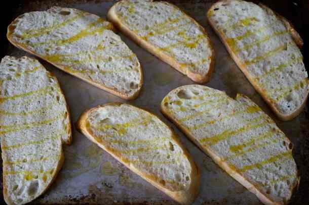 Slices of sourdough bread for tartines drizzled with olive oil on a baking sheet.