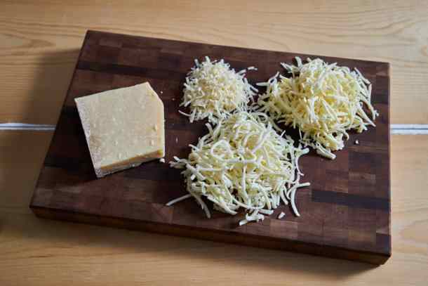 Grated fontina, mozzarella and parmigiano reggiano cheese on a wooden cutting board.