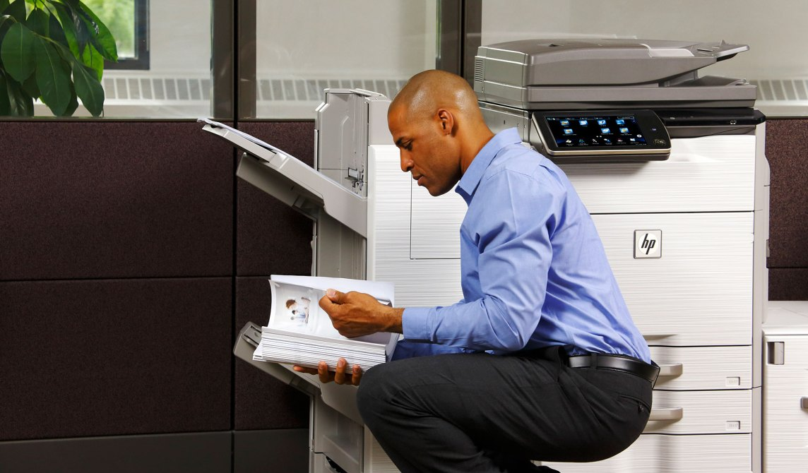 Man reading documents by an HP copier