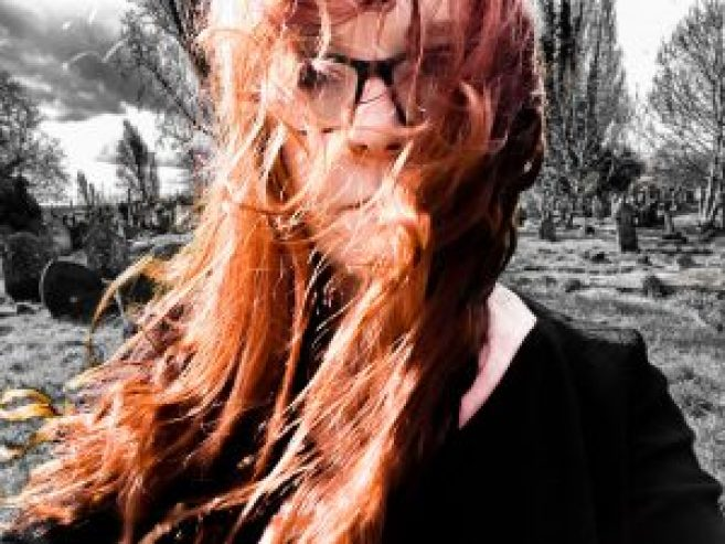A red-haired woman with glasses standing in Kensal Green Cemetery in London.