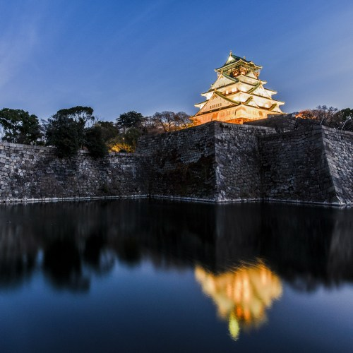 Castle in Osaka after sunset with reflection