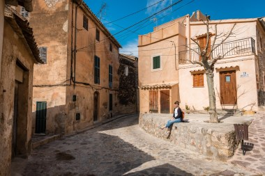 A girl is sitting on a wall surrounded by orange houses in a small village on the island of Mallorca