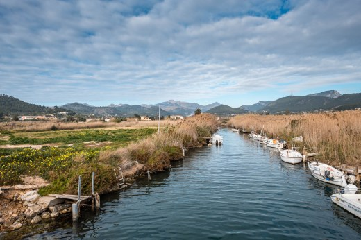 A stream with small motor boats on it and mountains in the background