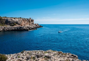 A boat drives to the harbour on a sunny day on the island of Mallorca